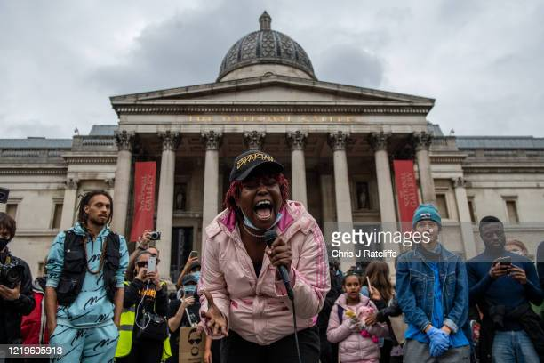 Black Lives Matter supporter sings to crowds who marched with her in front of the National Gallery in Trafalgar Square on June 12, 2020 in London,...