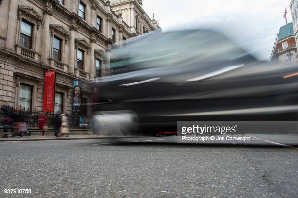 A black London cab speeds past the camera in a London street