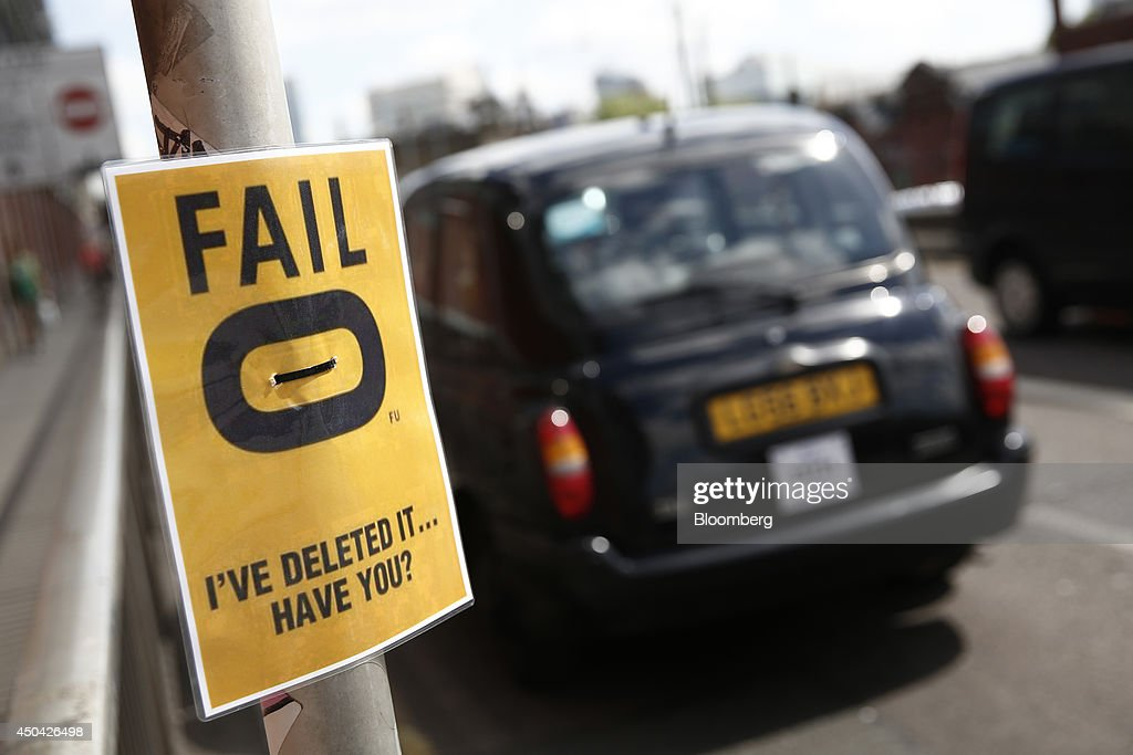 A black London taxi cab passes a poster protesting against the Hailo smartphone app outside Waterloo train station, ahead of a protest against Uber Technologies Inc.'s car sharing service, in London, U.K., on Wednesday, June 11, 2014. More than 30,000 taxi and limo drivers from London to Milan plan to cause traffic snarls in tourist centers and shopping districts, in protest against the unregulation of Uber's car-sharing service. Photographer: Simon Dawson/Bloomberg via Getty Images