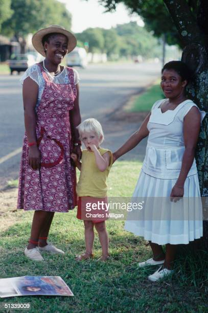 A black maid in Johannesburg spends time with her white charge and a friend circa 1985