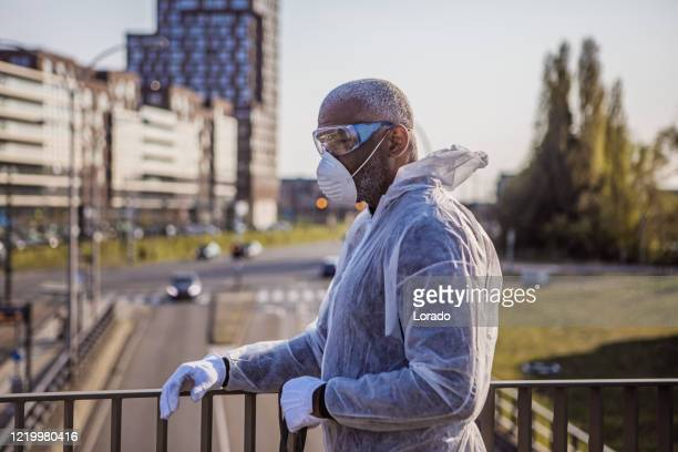 a black male essential worker wearing a face mask during virus outbreak - essential workers stock pictures, royalty-free photos & images