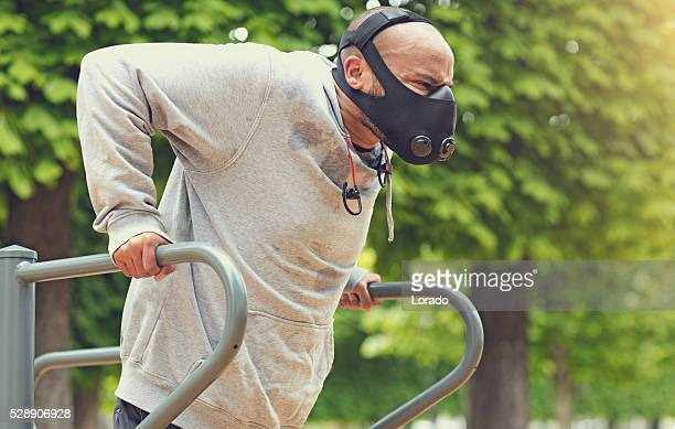 Black male exercising Paris park Spring afternoon wearing breathing apparatus
