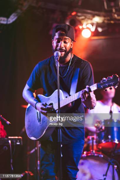 black male guitarist singing and playing acoustic guitar on stage - pop musician stock pictures, royalty-free photos & images