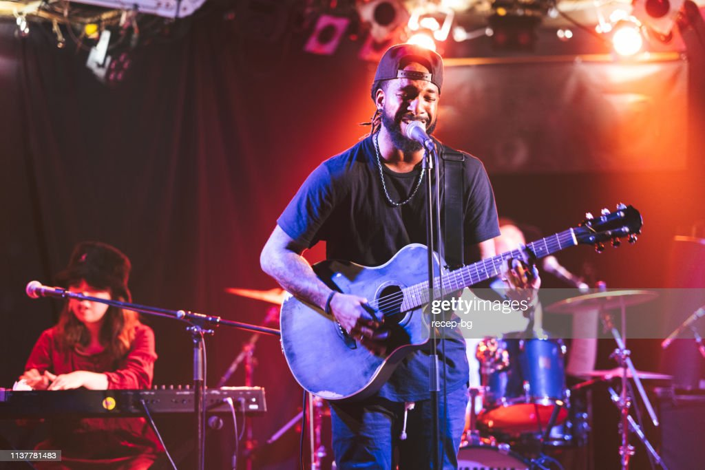 Black male guitarist singing and playing acoustic guitar on stage : Stock Photo