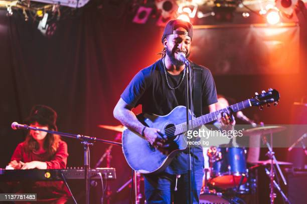 black male guitarist singing and playing acoustic guitar on stage - performance group stock pictures, royalty-free photos & images