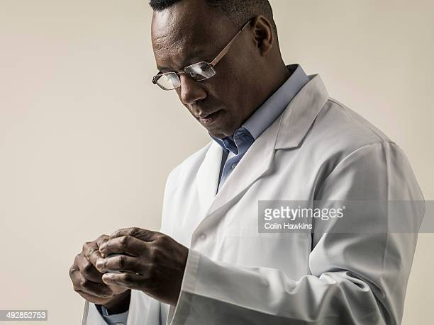 black male in lab coat examining object - healthcare stock pictures, royalty-free photos & images