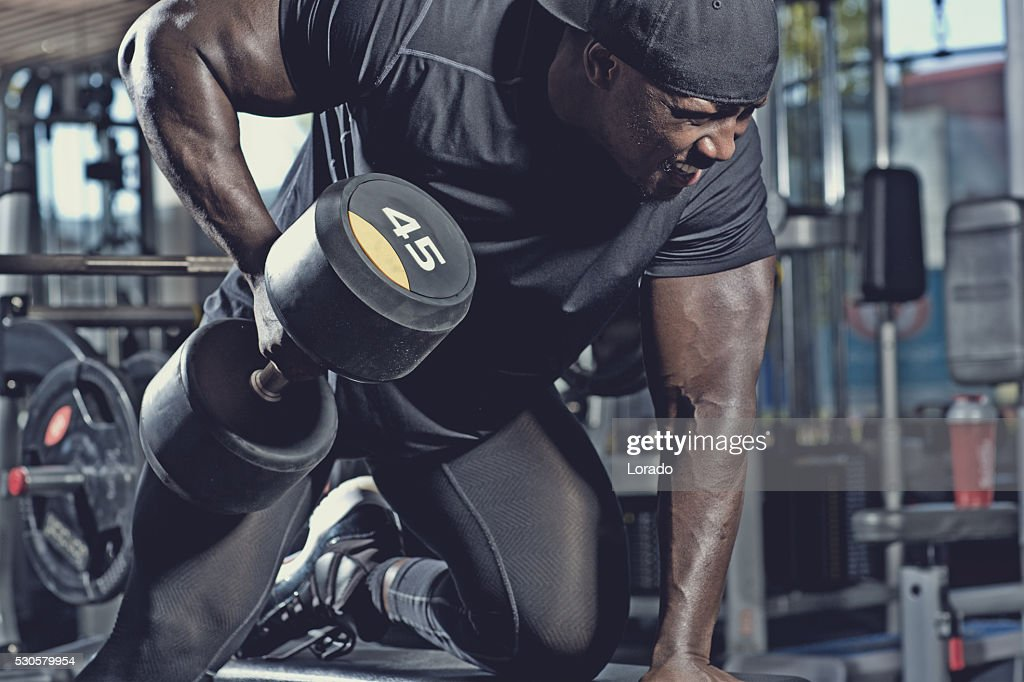 black male lifting dumbbells at a gym : Stock Photo