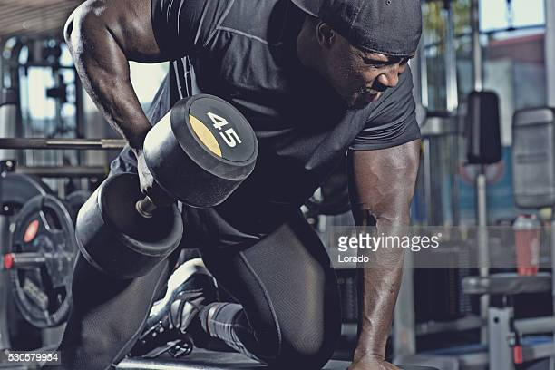 black male lifting dumbbells at a gym
