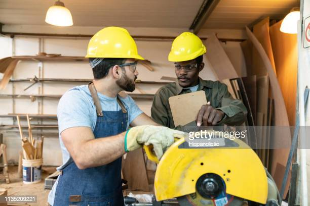 black male manager talking to employee holding a circular saw at a factory - hispanolistic stock photos and pictures