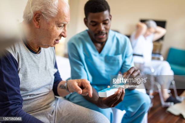 black male nurse giving instructions to senior patient when to take his pills - nursing assistant stock pictures, royalty-free photos & images
