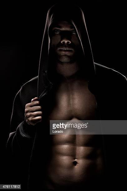 Black male posing in a hooded jacket