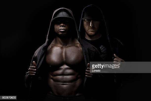 black male posing in a hooded jacket with white male - black male bodybuilders stock photos and pictures