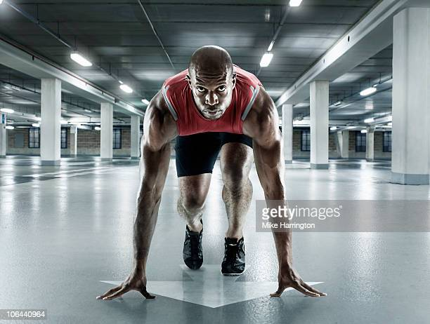black male sprinter in starting position - athletics stock pictures, royalty-free photos & images