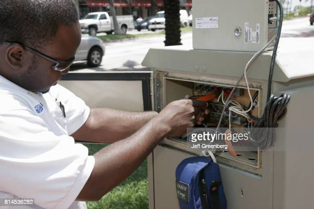 A Black male technician repairing a traffic signal control box at Miami Beach