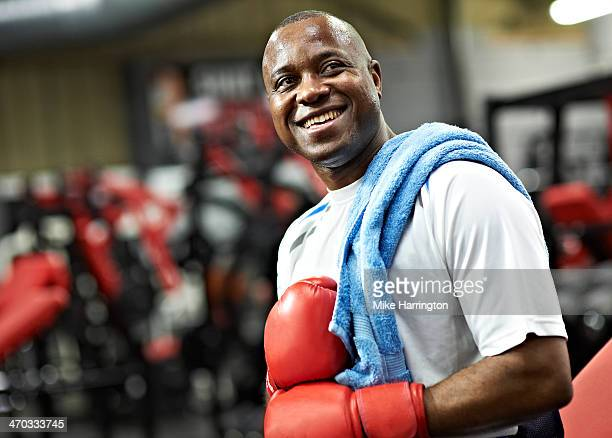 black male wearing boxing gloves in gym - boxing stock pictures, royalty-free photos & images