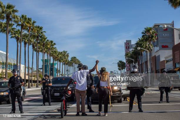 A black man and a white woman hold their hands up in a front of police officers in downtown Long Beach on May 31 2020 during a protest against the...