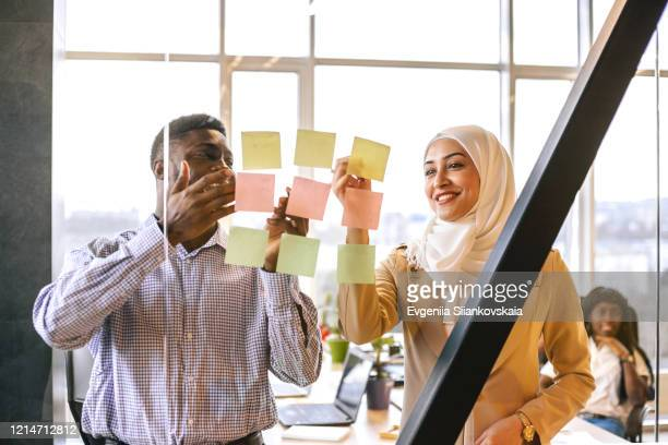 black man and muslim woman discuss their project with a help of pictures. - diversity stock pictures, royalty-free photos & images