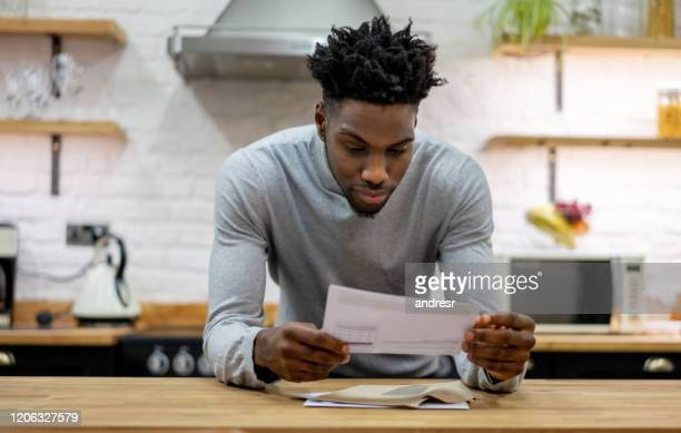 black man at home reading the mail - text stock pictures, royalty-free photos & images