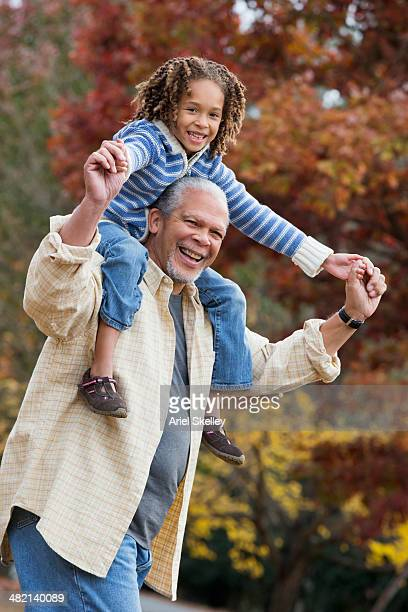 Black man carrying granddaughter on shoulders