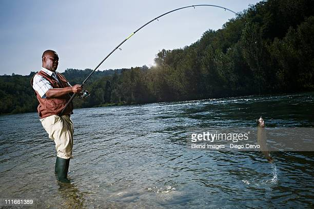 black man catching fish in stream - fishing tackle stock pictures, royalty-free photos & images