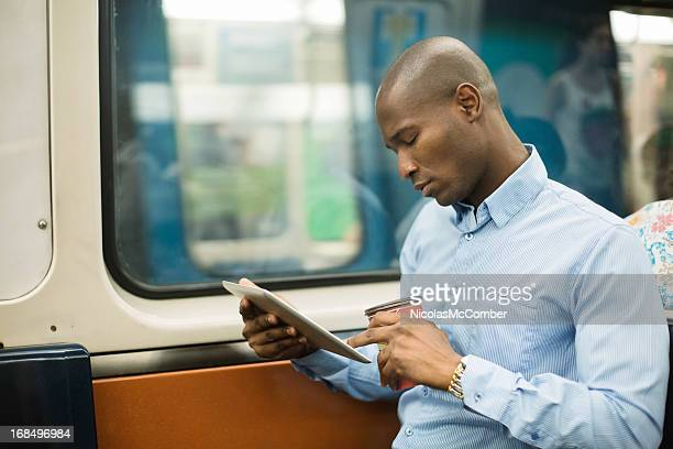 Black man commuting on subway with digital tablet