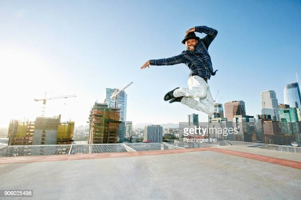 black man dancing and jumping on urban rooftop - one mid adult man only stock pictures, royalty-free photos & images
