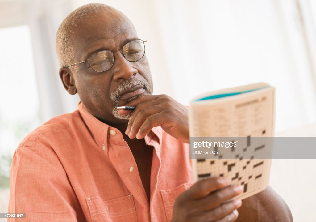 Black man doing crossword puzzle : Stock Photo