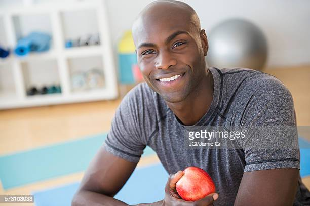 Black man eating apple in gym