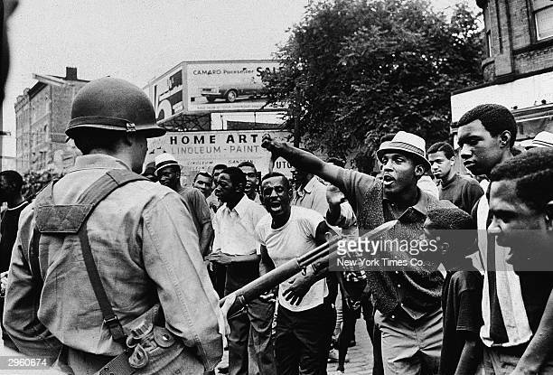 A Black man gestures with his thumb down to an armed National Guardman during a protest in the Newark race riots Newark New Jersey July 14 1967