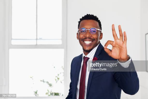 Black man gesturing okay in gallery