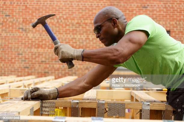 Black man hammering nail at construction site