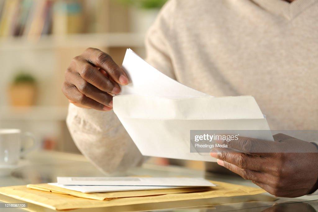 Black man hands putting a letter inside an envelope : Stock Photo