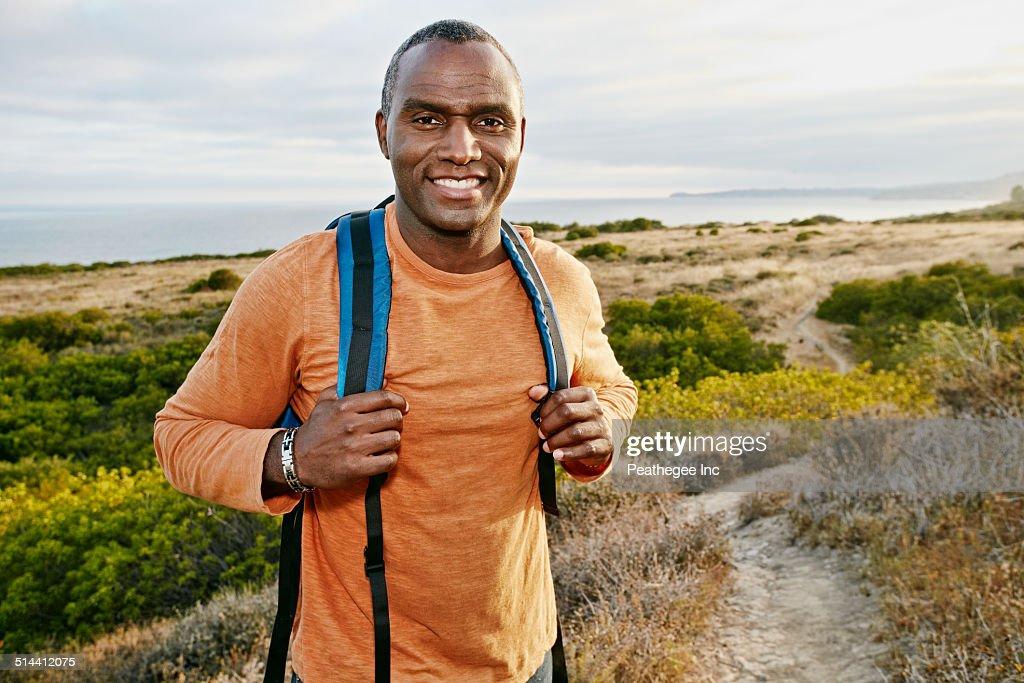 Black man hiking on rural path : Stock Photo