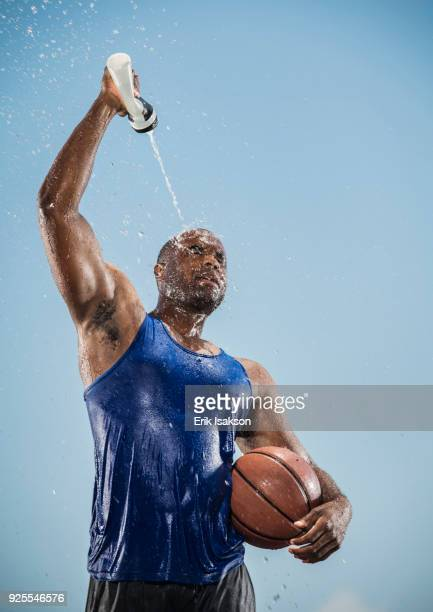 black man holding basketball cooling off with water bottle - squirt foto e immagini stock