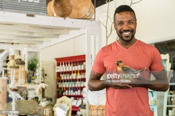 Black man holding bird statue in antique store