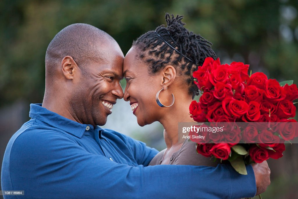 Black man hugging wife and giving her red roses : Stock Photo