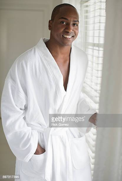 Black man in bathrobe standing at window