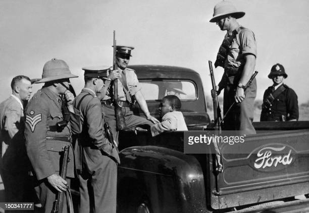 Black man is arrested and kept in a Ford police car as violence increased in East London, in November 1952. - Riots erupted in East London, Eastern...