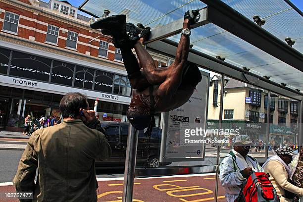 CONTENT] A black man is performing acrobatic tricks hanging on a bus stop while the other man is talking on his mobile phone without paying much...