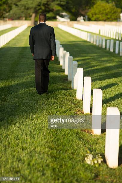Black man leaving bouquet at gravestone at military cemetery
