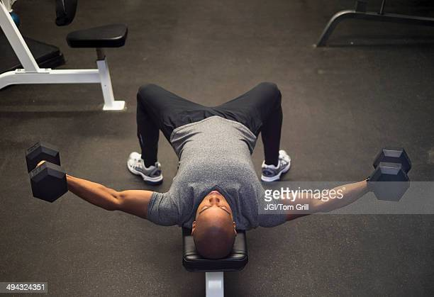 Black man lifting weights in gym