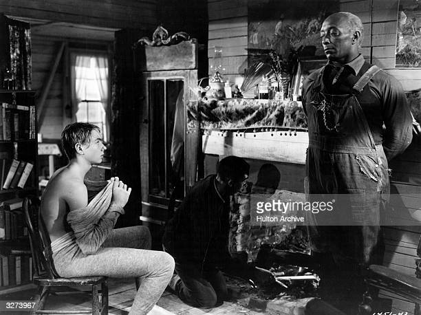 A black man lights the fire while his colleague stands by the fireplace talking with a white boy in a scene from the film 'Intruder In The Dust'...