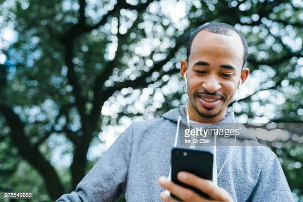 Black man listening to cell phone with earbuds