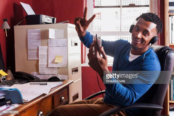 Black man listening to cell phone with headphones