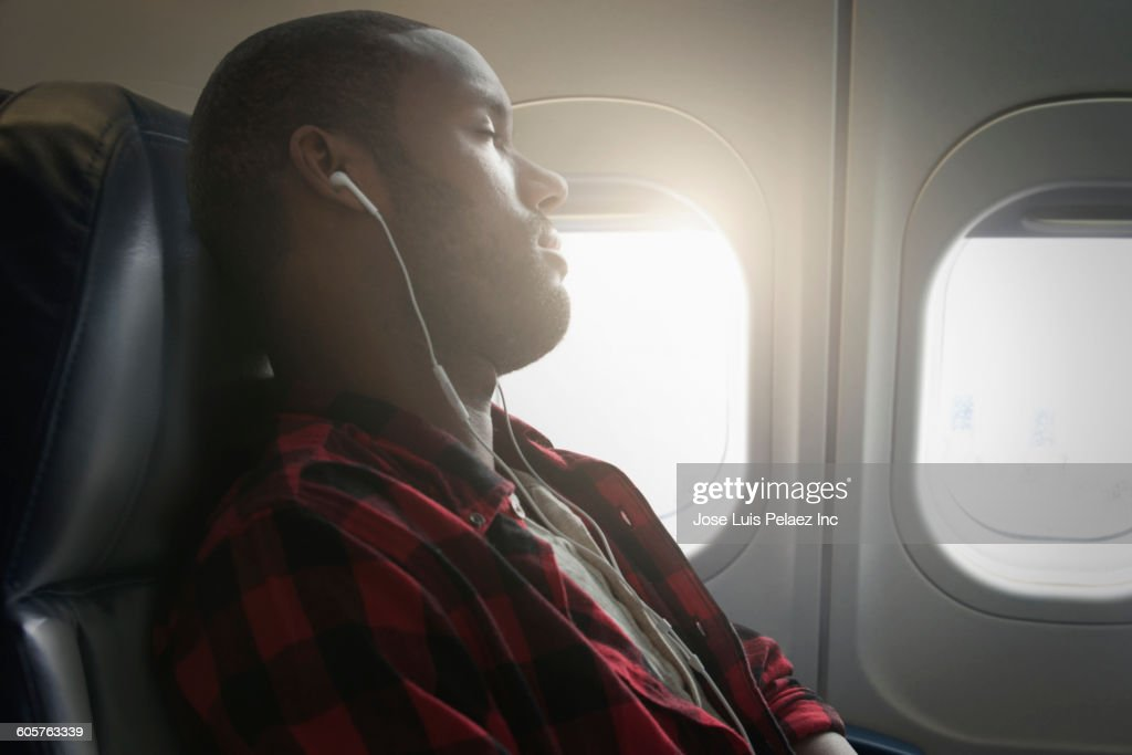Black man listening to earbuds on airplane : Stock Photo
