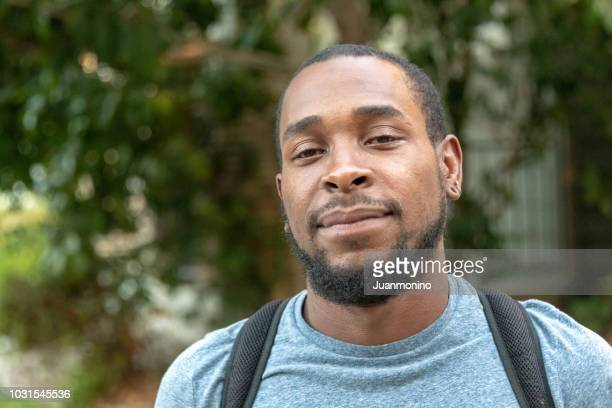 black man looking at the camera wearing a backpack - afro caribbean ethnicity stock pictures, royalty-free photos & images
