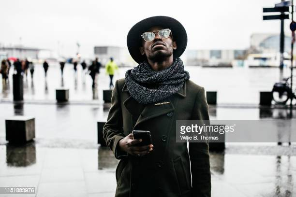 black man looking up while holding smartphone - gray coat stock pictures, royalty-free photos & images