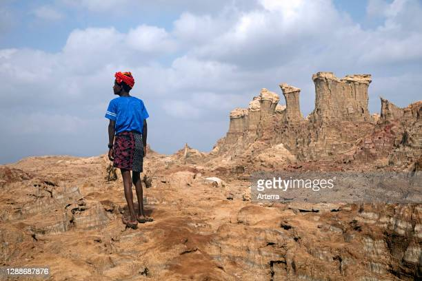 Black man of the Afar tribe and towers and pinnacles composed of salt, potassium and magnesium in the Danakil Desert, Ethiopia, Africa.