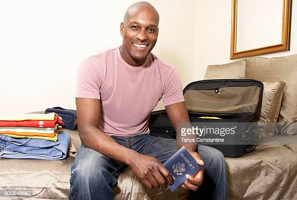 Black man packing passport for trip