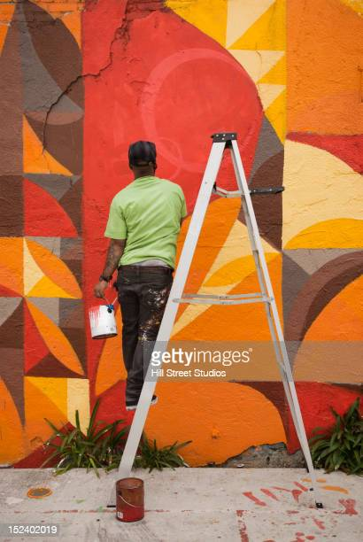 Black man painting wall